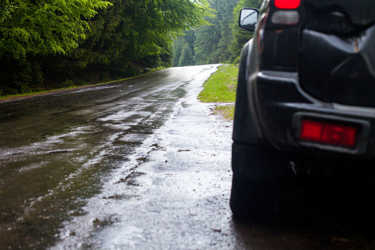 Wet road after rain and car standing on the roadside in the forest Car Close-up Day Land Vehicle Mode Of Transport Motorsport Nature No People Outdoors Rain Road The Way Forward Transport Transportation Travel Tree Vehicle Wet WoodLand
