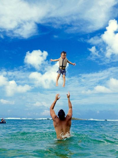 Rear View Of Father And Son Playing In Sea