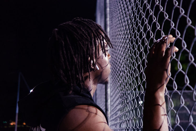 Side view of young man looking through chainlink fence at night
