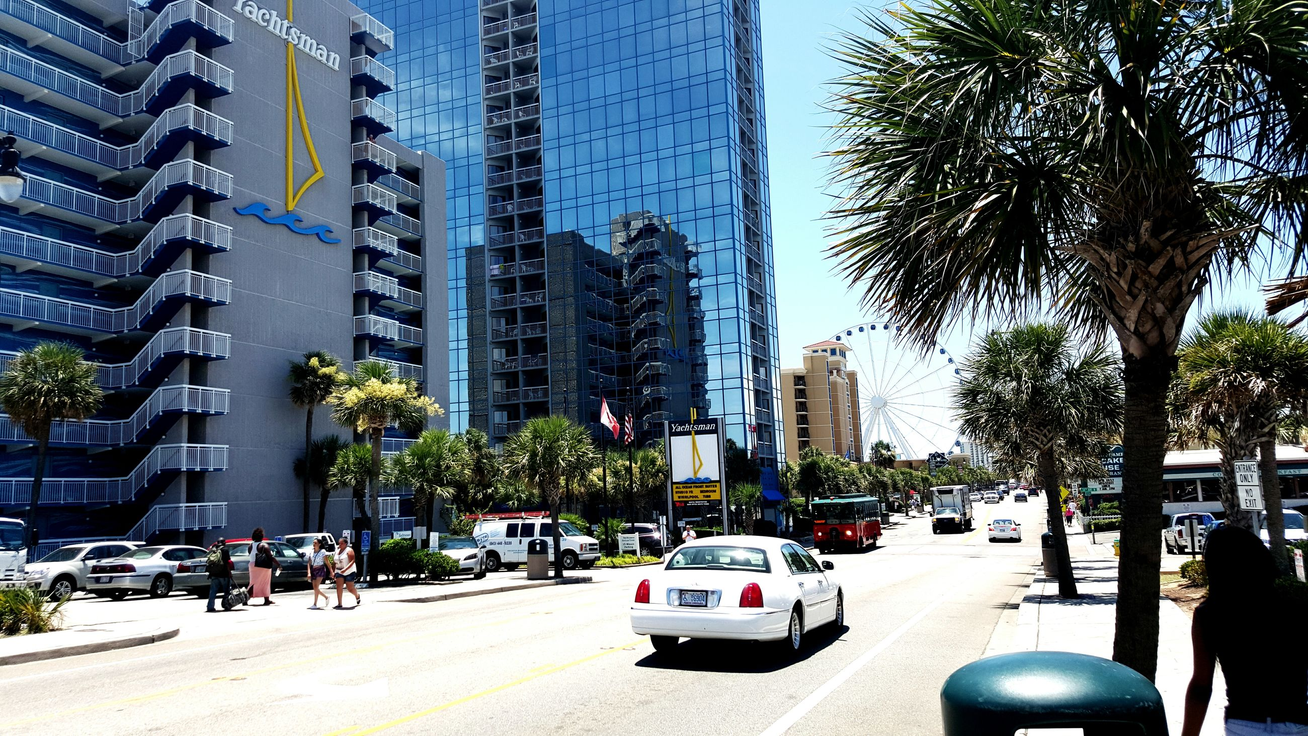 building exterior, architecture, built structure, city, tree, car, street, city life, land vehicle, transportation, sunlight, incidental people, building, mode of transport, day, shadow, sky, outdoors, clear sky, residential building
