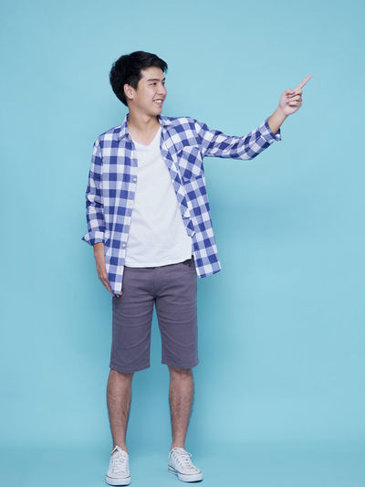 Full length of young man standing against blue background