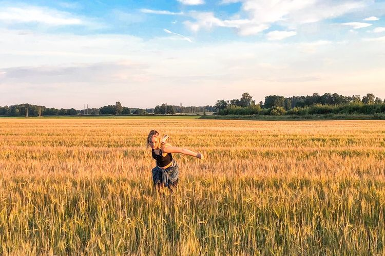 Woman with arms raised on field against sky