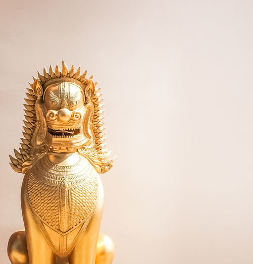 An Old thai chinese golden lion statue under sunlight with warm color wall background. Antique Architecture Copy Space Light Reflection Sunlight Backgrounds Chinese Close-up Day Gold Gold Colored Indoors  Light And Shadow No People Old Religion Religious Architecture Sculpture Shadow Shiny Space Spirituality Statue Tiger