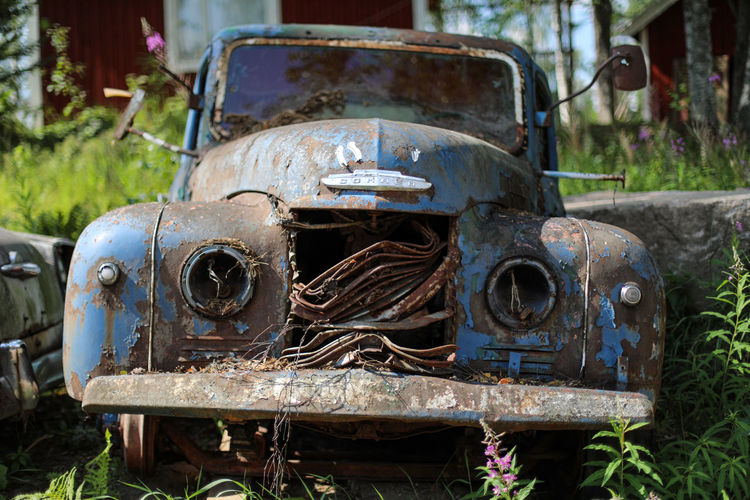 Close-up of abandoned vintage car on field