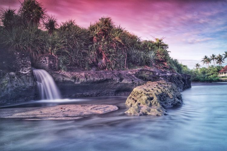 Scenic view of waterfall by rock formation