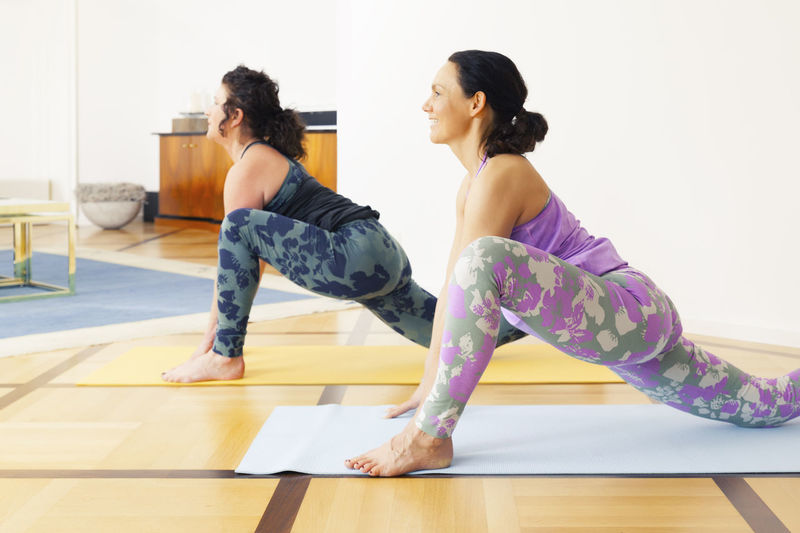 Side view of women exercising on mat at home