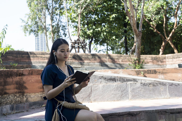 Full length of young woman using phone while sitting on tree