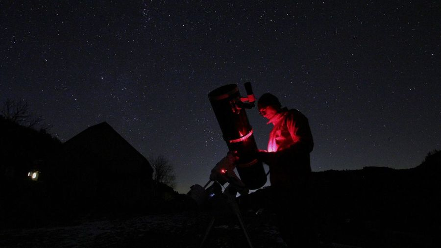 Man using mobile phone by telescope against sky at night