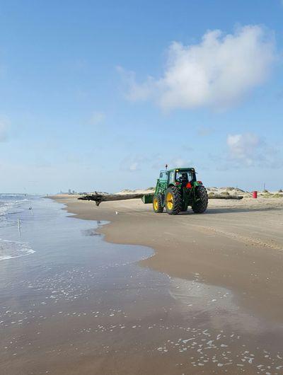 Bulldozer At Beach Against Sky