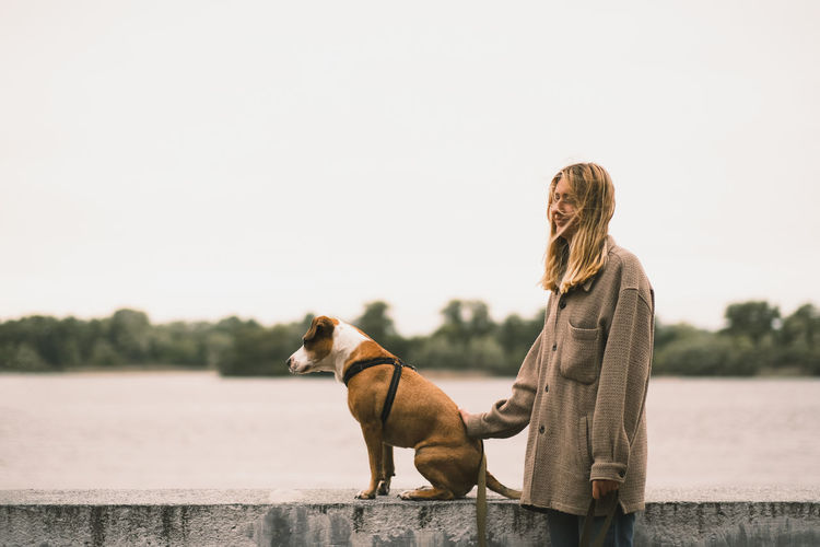 Side view of woman with dog against lake