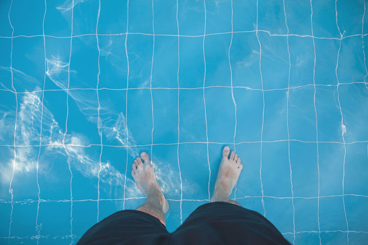 Low section of man standing in swimming pool