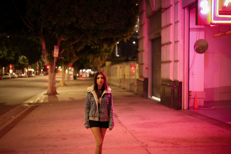 Woman standing on street at night
