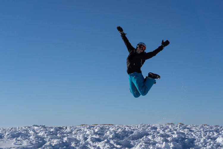 Woman jumping on snow covered land against blue sky