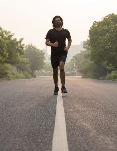 Front view of a man wearing a mask while running on an empty road during sunrise.