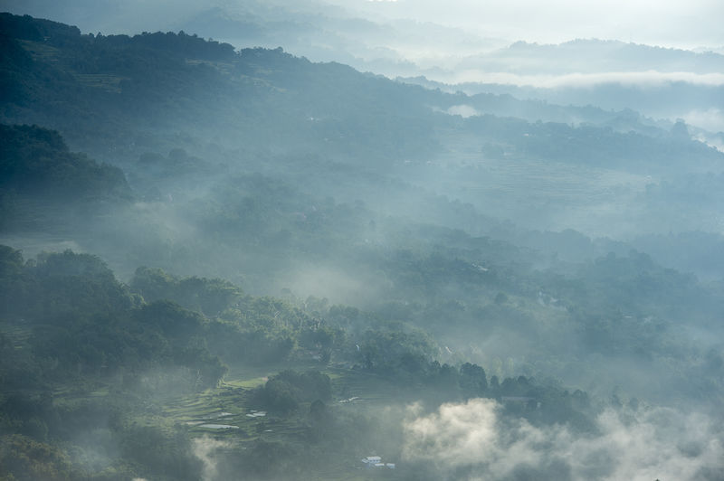 Aerial view of foggy green mountainous landscape at dawn