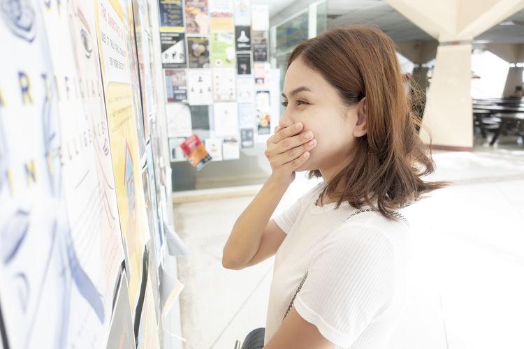 Smiling woman reading document on bulletin board in corridor