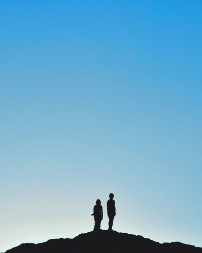 REAR VIEW OF SILHOUETTE PEOPLE AGAINST CLEAR SKY
