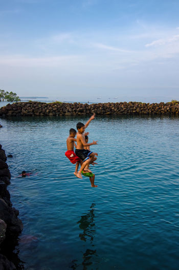 Happy Kids Beauty In Nature Cloud - Sky Day Full Length Jumping Leisure Activity Lifestyles Men Nature Outdoors People Real People Scenics - Nature Sea Shirtless Sky Togetherness Two People Water Waterfront