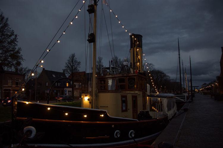 Sailboats moored on illuminated street against sky at dusk