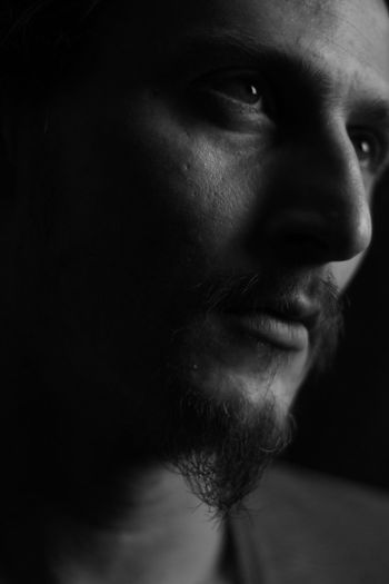 Close-up of young man looking away against black background