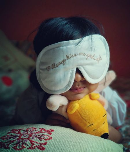 Close-up of cute girl wearing sleep mask holding stuffed toy on bed at home