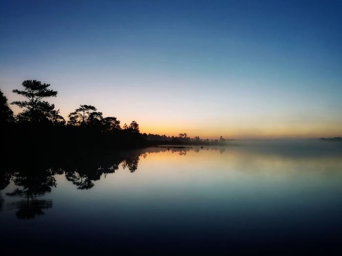sunrise Reflection Sunset Silhouette Sky Water Lake Nature Scenics Tree Outdoors No People Landscape Tranquility Sun Blue Beauty In Nature Multi Colored Dawn Horizon Over Water