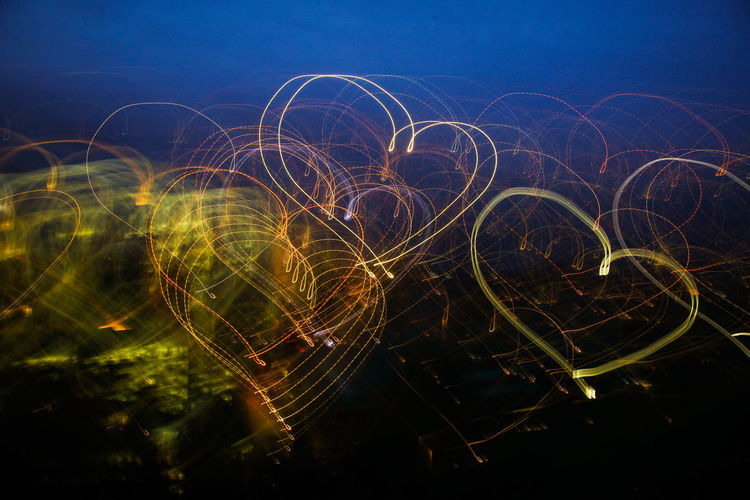 Close-Up Of Heart Shapes Light Trails Against Sky At Night