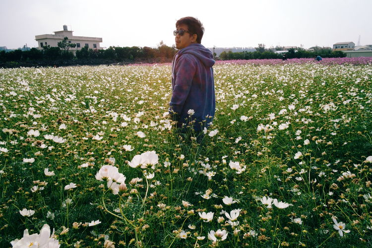 Side View Of Young Man Standing Amidst Flowering Plants On Field
