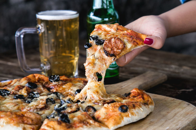 Close-up of hand holding pizza on table