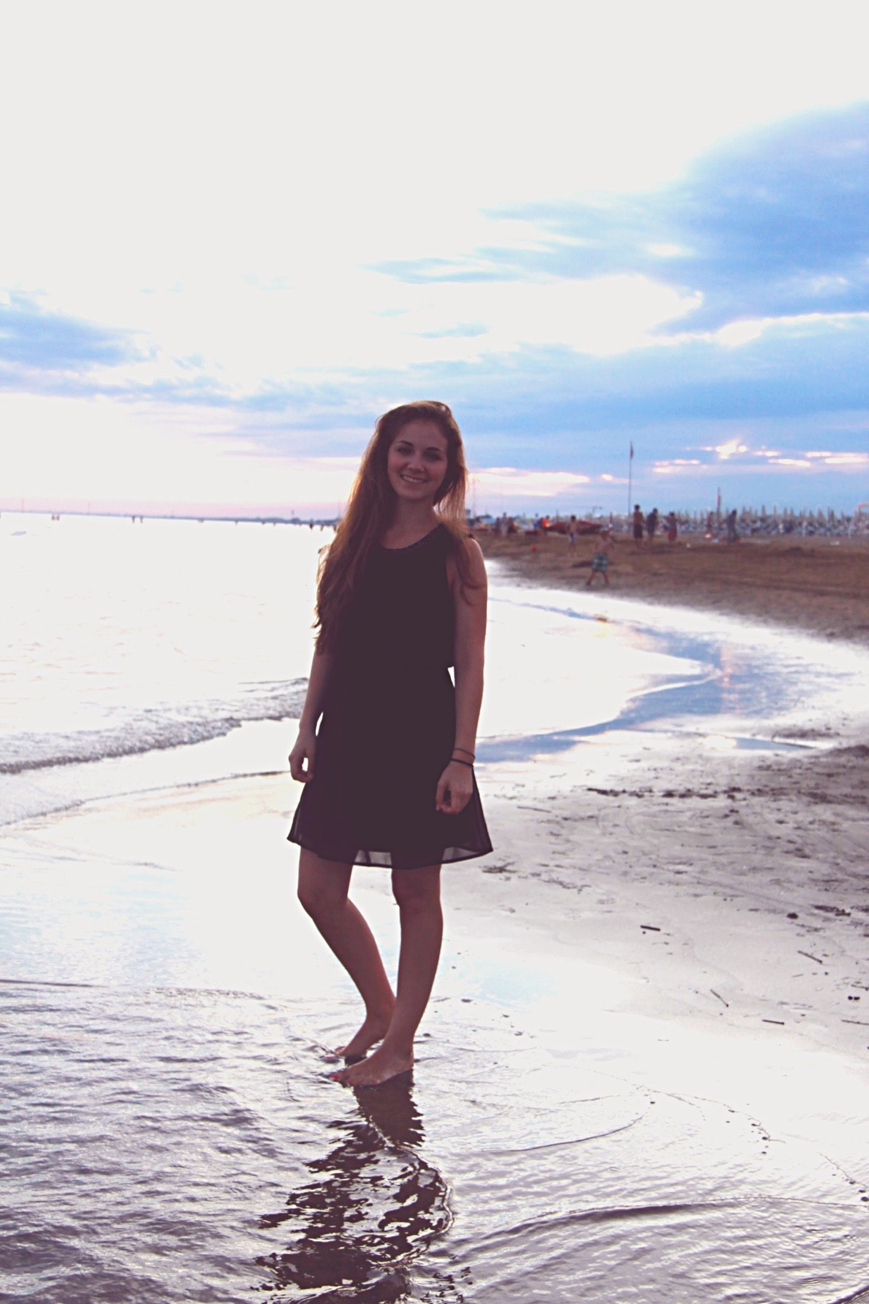 young adult, beach, person, lifestyles, young women, water, leisure activity, looking at camera, portrait, sea, full length, standing, front view, casual clothing, sky, shore, sand, long hair