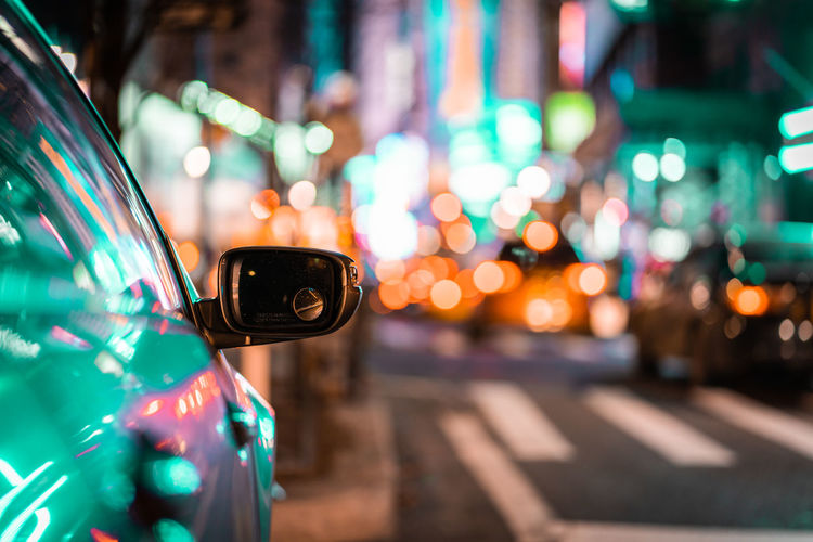 Close-up of illuminated cars on road at night