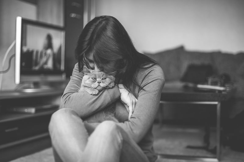 Side view of woman holding cat while sitting at home