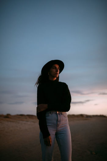 Young woman looking away while standing on land against sky during sunset