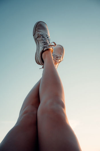 Low section of woman legs against clear sky