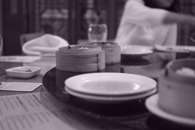 Close-up of plates and food in containers with woman sitting in background