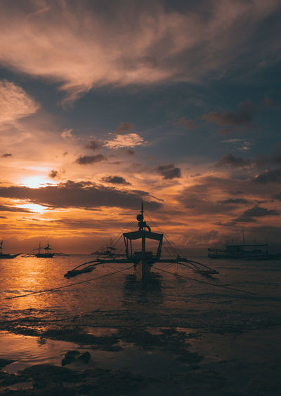 Outrigger boat in sea against sky during sunset