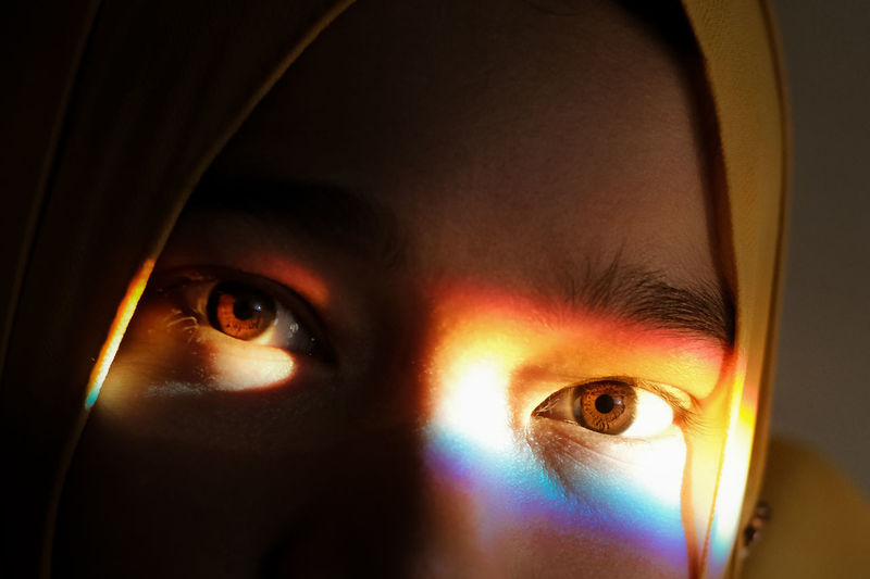 Close-up portrait of woman with spectrum on eye