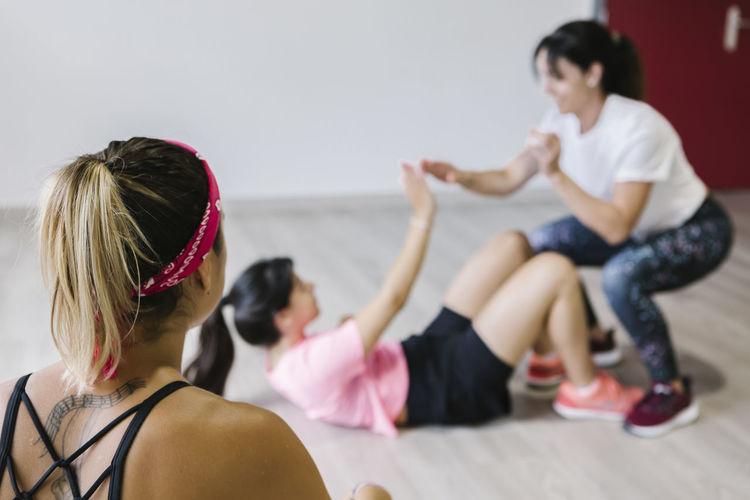 Rear view of women sitting on floor