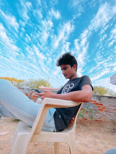 Young man sitting on seat against sky
