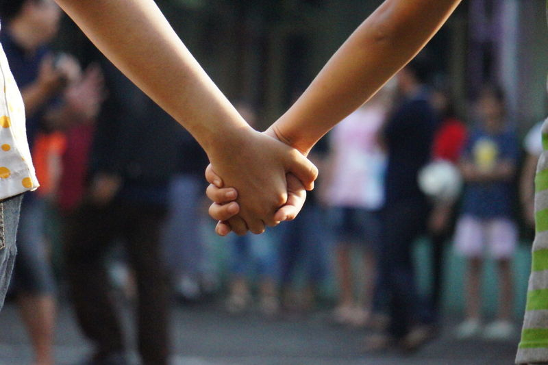 Midsection Of Friends With Holding Hands