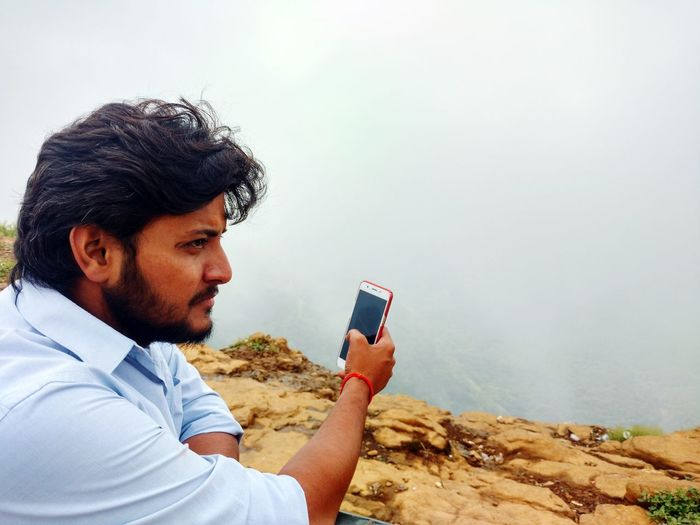 Young man taking selfie from mobile phone at mountain peak