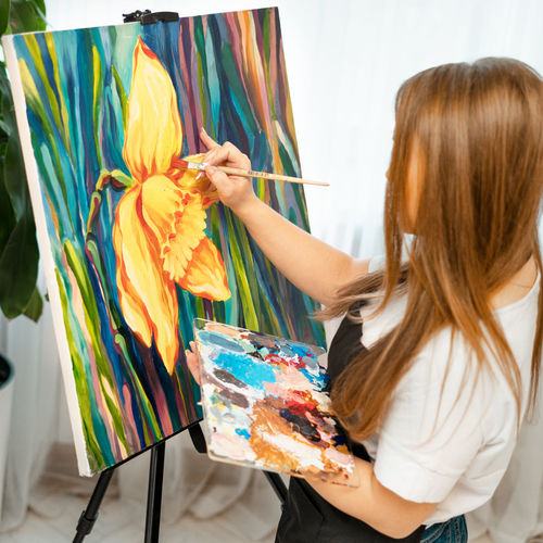 Side view of woman with long hair painting on canvas