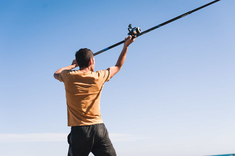 Rear view of man holding fishing rod while standing against sky during sunny day