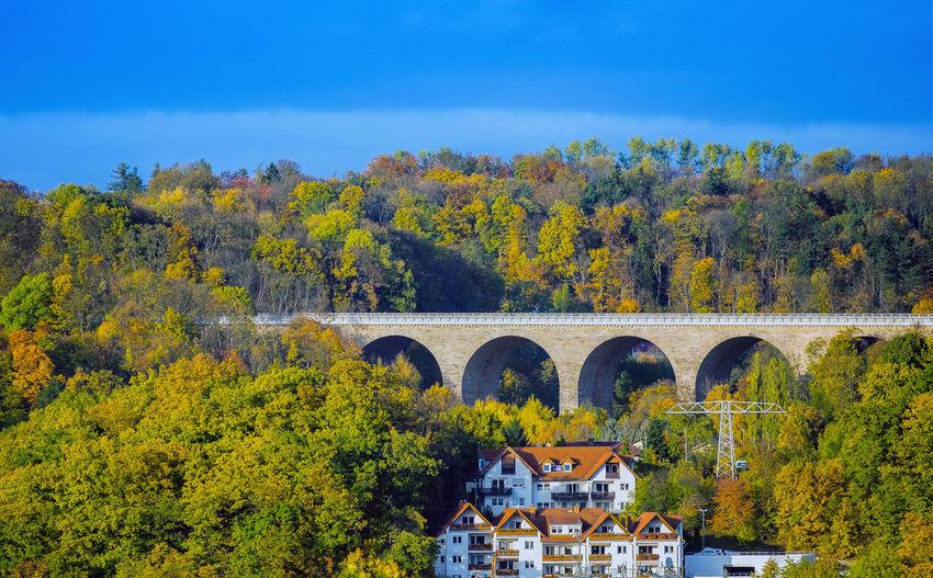Arch bridge over trees against sky during autumn