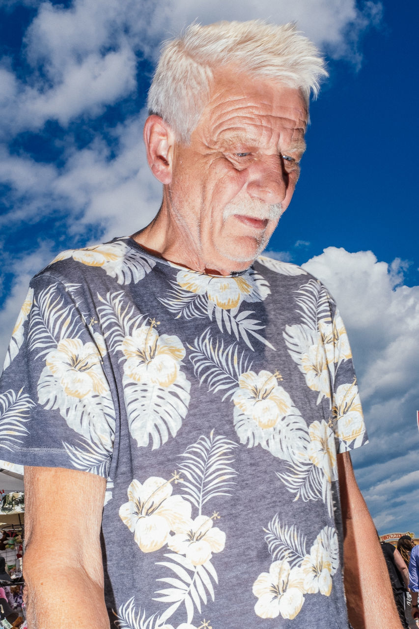 LOW SECTION OF MAN STANDING AGAINST THE SKY