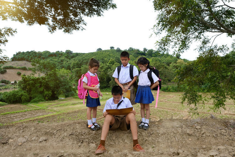 Siblings standing by brother reading while sitting on field against trees