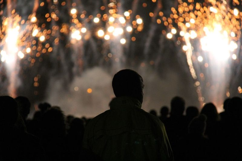 Silhouette people standing on field during firework display at night