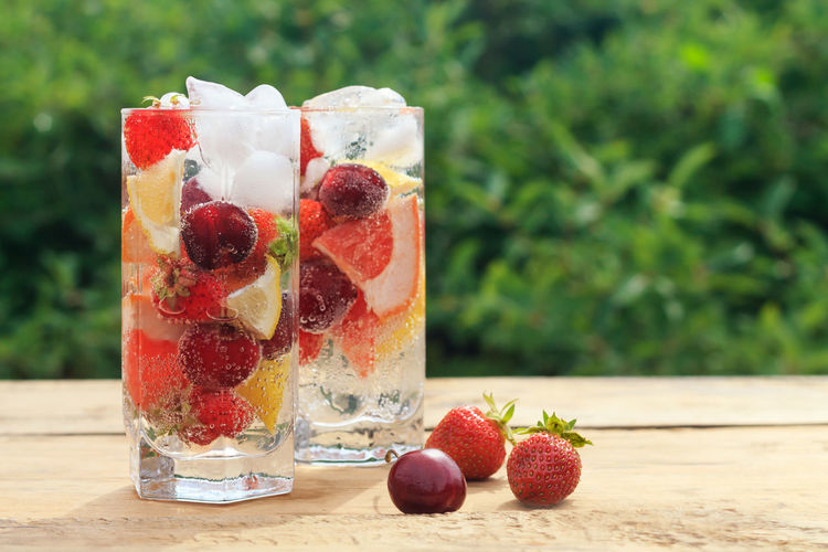 Summer fresh drink with mineral water with ice, berries and fruits (strawberry, cherry, lemon, grapefruit) on a natural green background on a wooden table. Blurred Cherry Cocktail Copy Space Natural Red Aerated Background Close-up Daylight Drink Drinking Glass Fizzy Water Freshness Fruit Grapefruit Greens Healthy Eating Lemon Mineral Water Strawberry Summer Table Vegan Wooden