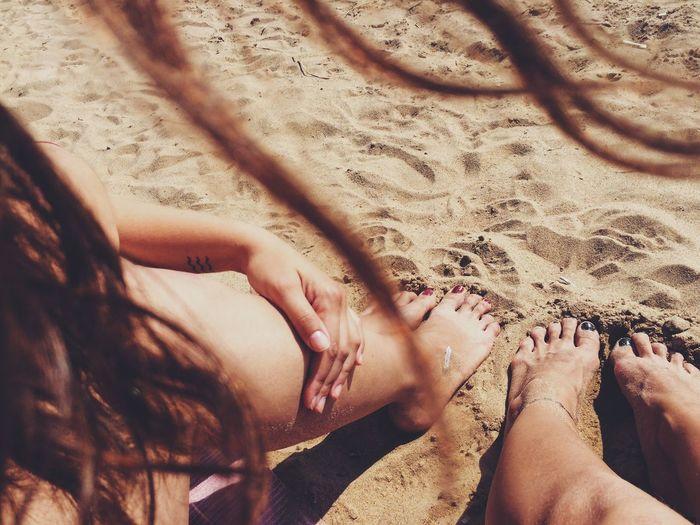 Legs of woman relaxing on beach