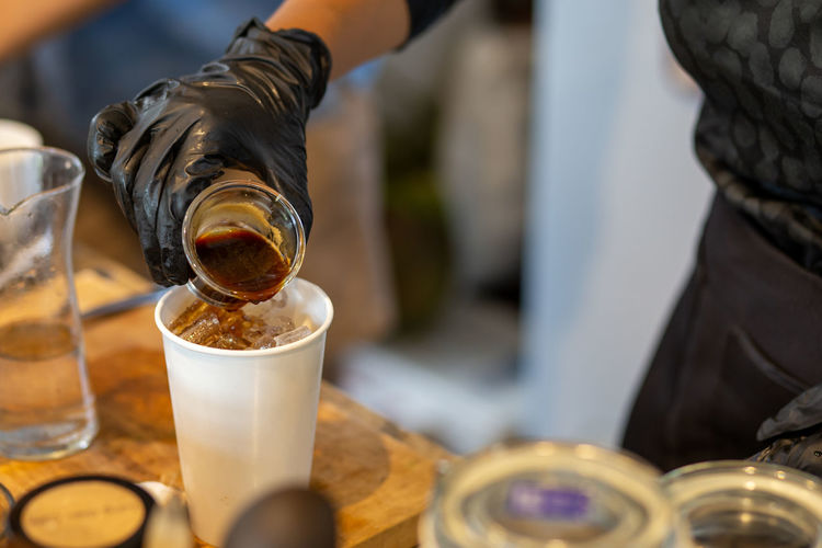 Close-up of hand pouring coffee in glass on table